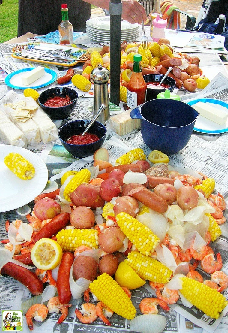 A party table with a spread of Cajun seafood boil with potatoes, corn, lemons, shrimp, and sausage.