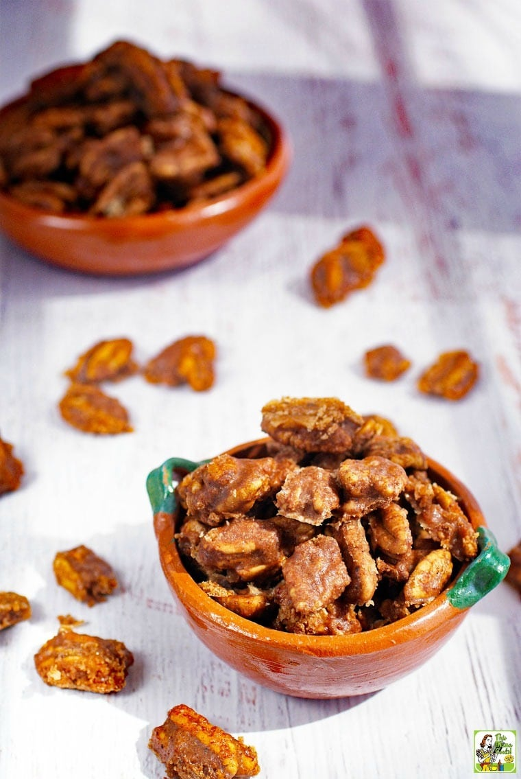 Bowls of Candied Pecans with pecans spread over the tabletop.