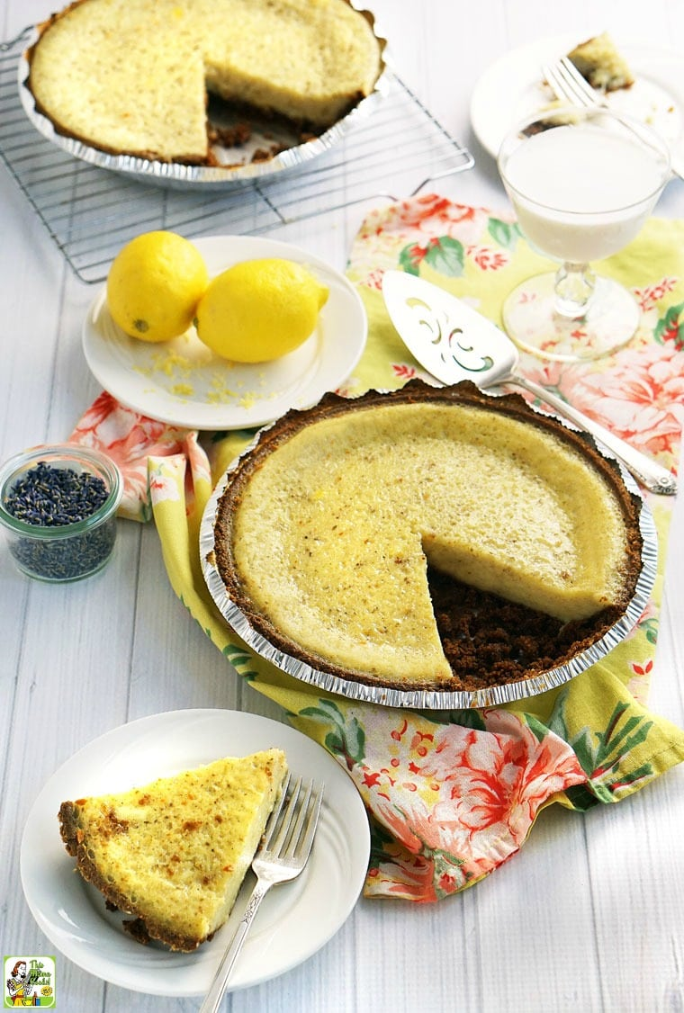A slice of old fashioned buttermilk pie on a white plate with fork with lemon and lavender.