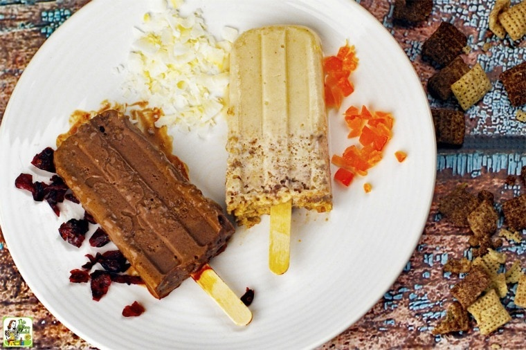 Two Homemade Ice Cream Bars on a plate with dried fruit, cereal, and coconut.