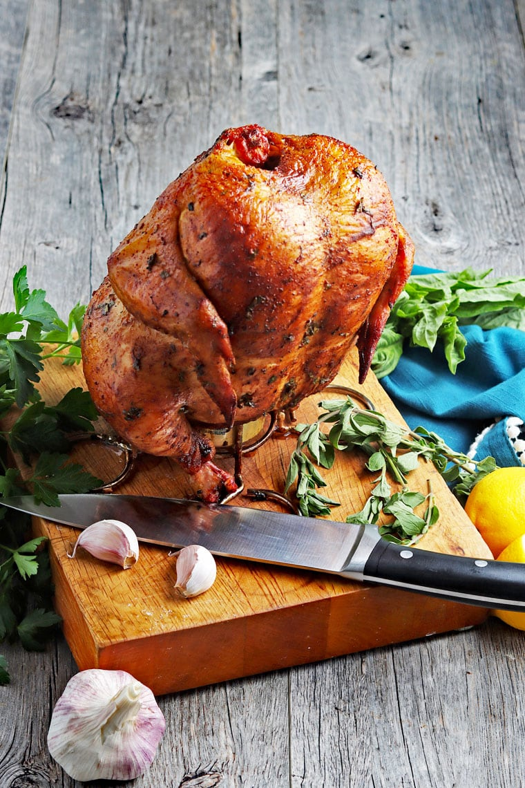 Smoked beer can chicken on a roaster rack placed on a cutting board with a knife with garlic cloves and herbs.