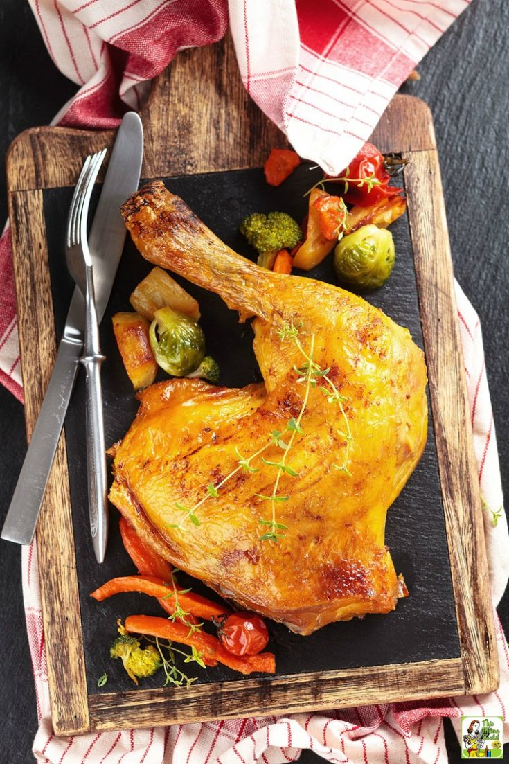 Smoked chicken quarters on a cutting board with a fork and knife with roasted vegetables.