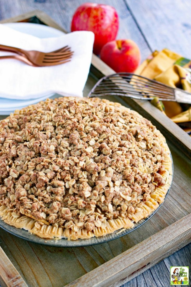 A peach pie with crumb crust on a wooden tray with plates, napkins, forks, apples, and a pie server.