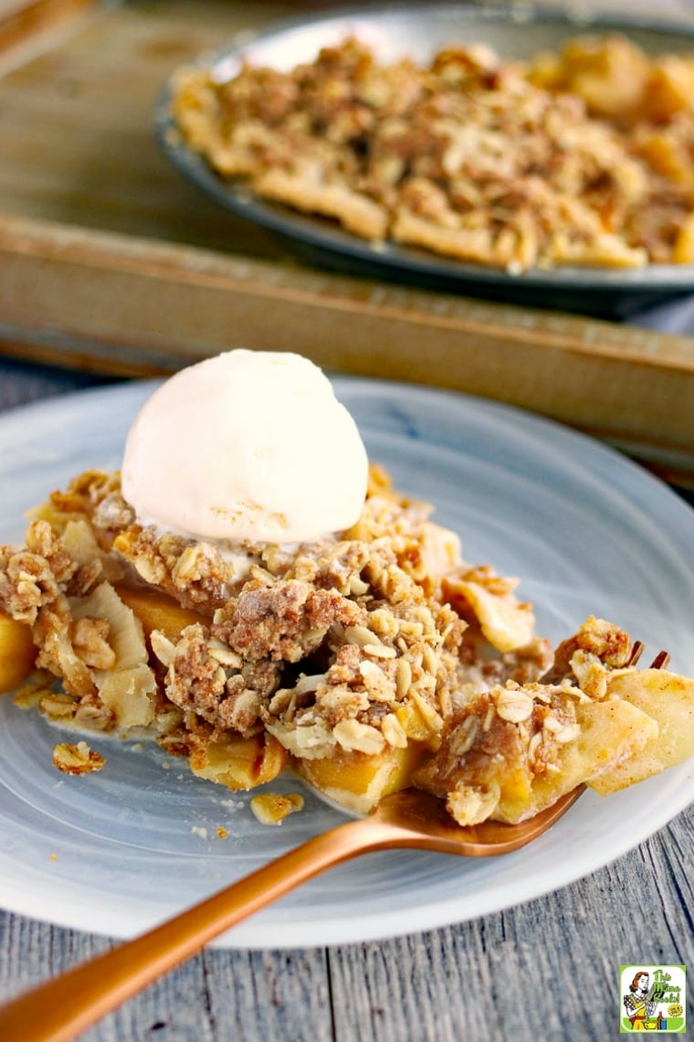 Closeup of a slice of peach and apple pie with a scoop of vanilla ice cream on a glass plate with a copper fork.