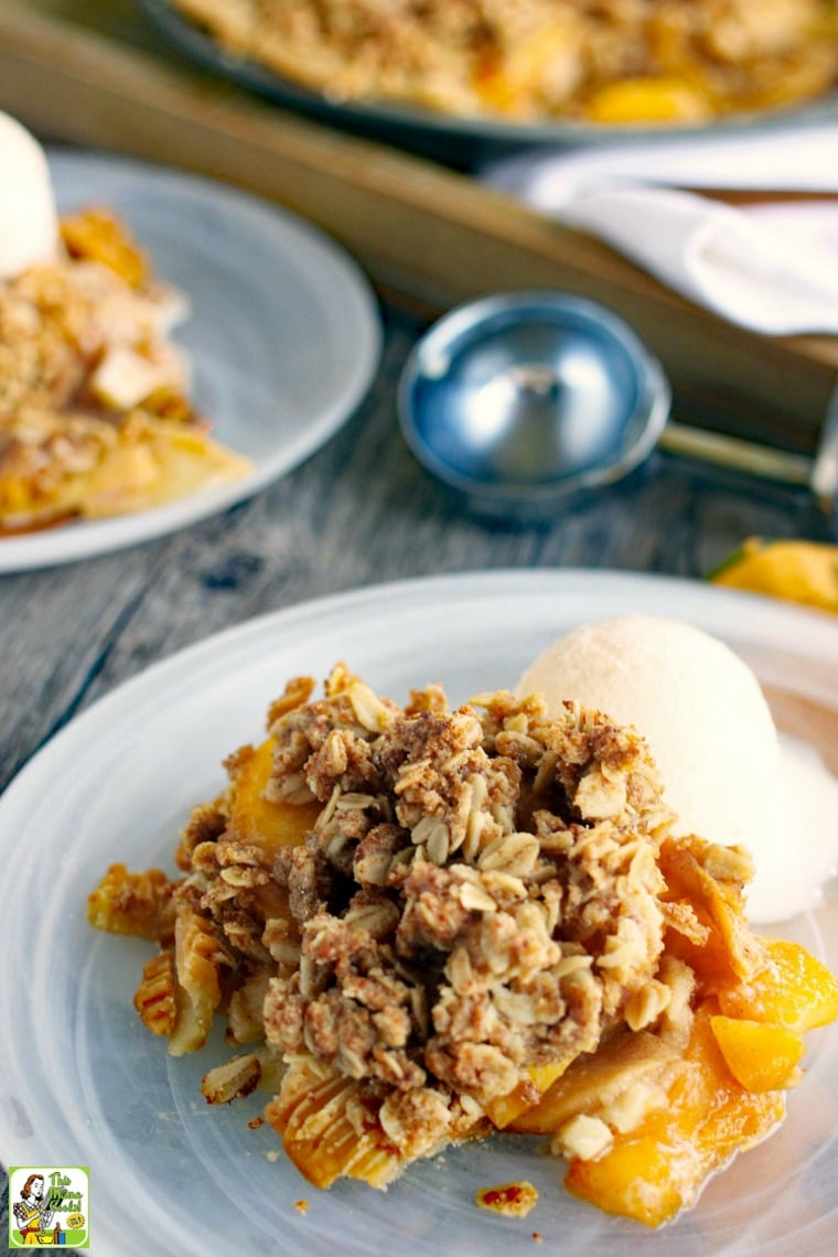 Peach pie with crumble topping with a scoop of vanilla ice cream on a glass plate with an ice cream scooper.