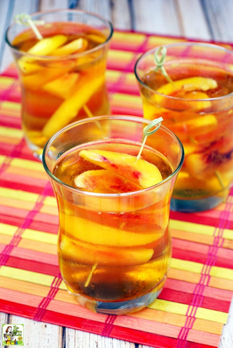 3 glasses of Peach Whiskey Cocktail with slices of peaches on bamboo skewers on a colorful bamboo placemat.