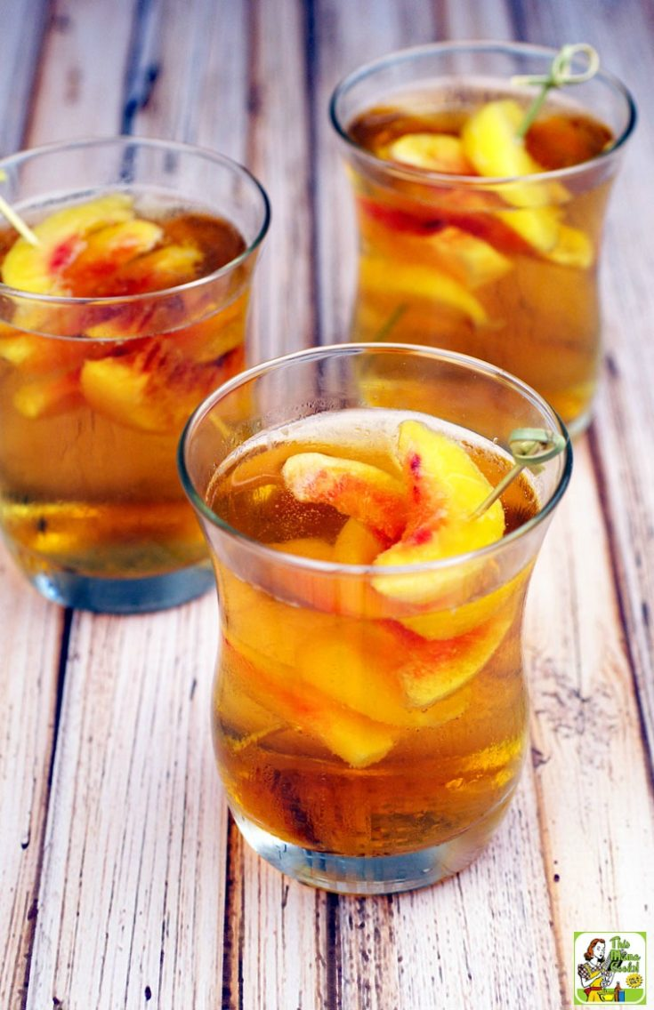 3 glasses of Peach Whiskey Cocktail with slices of peaches on bamboo skewers.