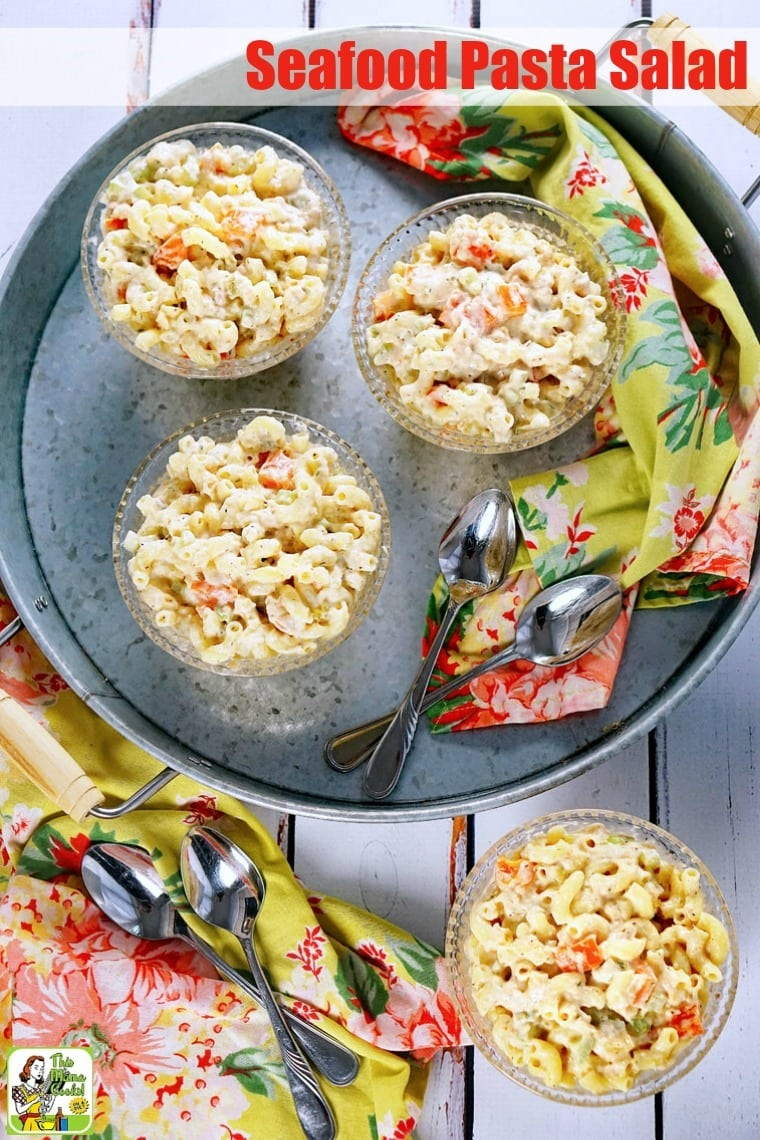 Overhead view of bowls of Seafood Pasta Salad on a metal tray with floral napkins and spoons.