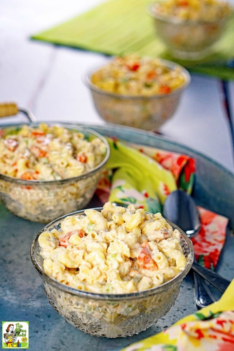 Bowls of Seafood Pasta Salad on a metal tray with floral napkins and spoons.