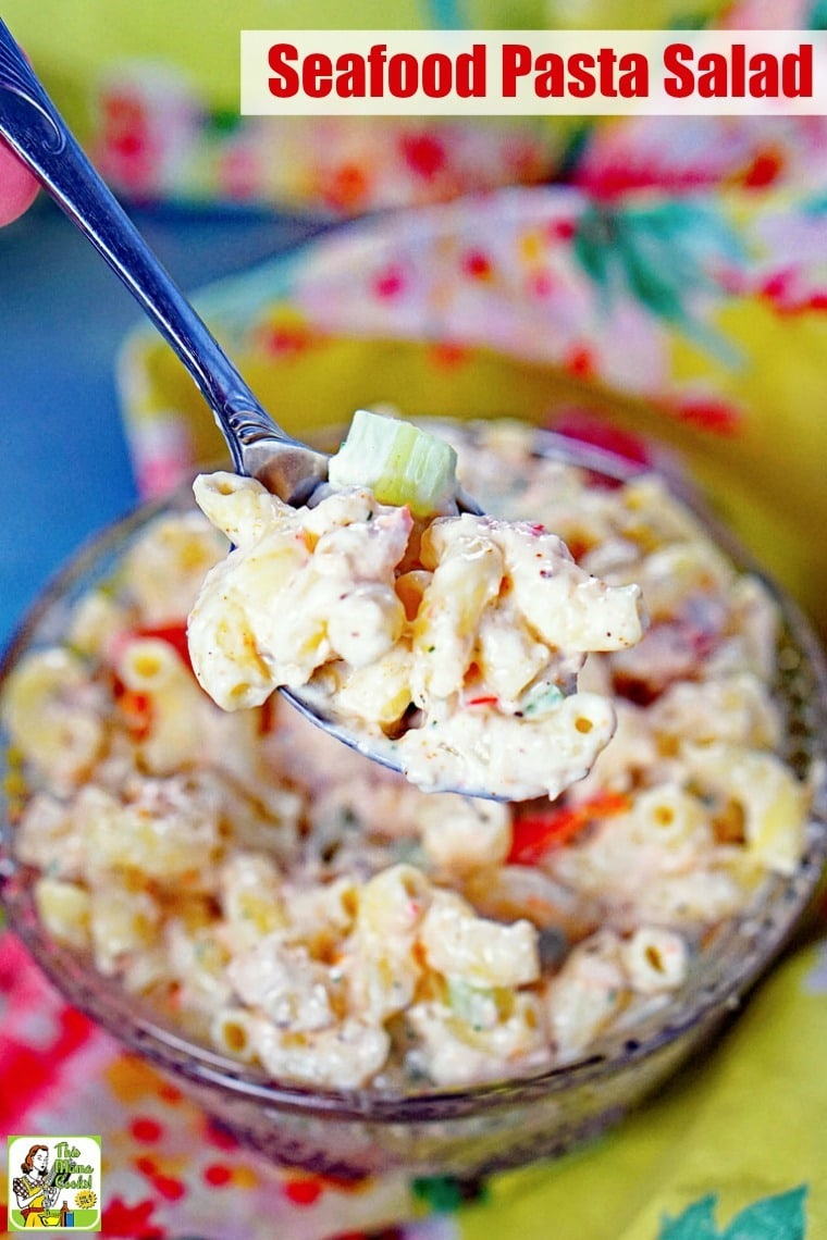A spoonful of Seafood Pasta Salad above a bowl.