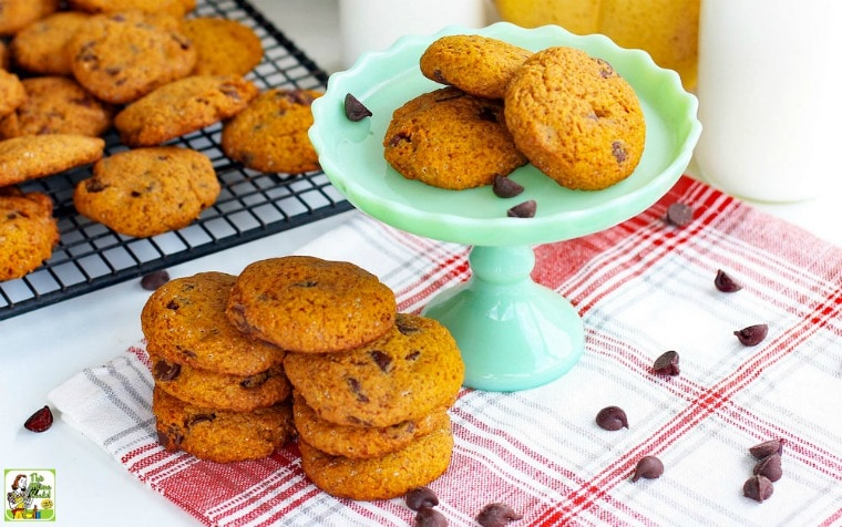 Stacks of Chocolate Chip Cookies on a green cake stand, baking rack, and a red and white napkin with pumpkins and milk bottles in the background.