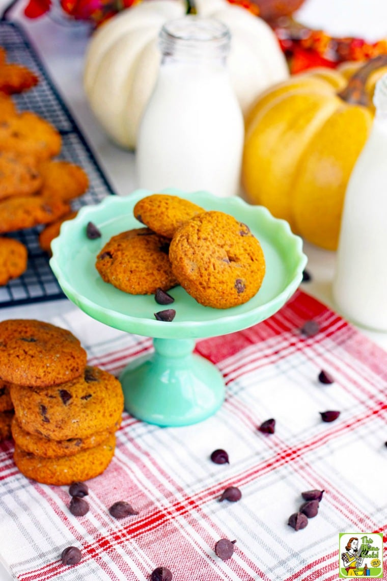 Chocolate Chip Cookies on a green cake stand, baking rack, and a red and white napkin with pumpkins and milk bottles.