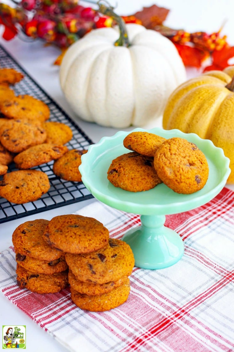Stacks of Chocolate Chip Cookies on a green cake stand, baking rack, and a red and white napkin with pumpkins in the background.
