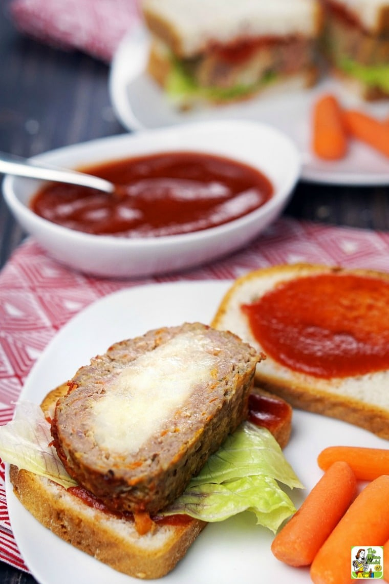 Plate of sliced mashed potato stuffed meatloaf served on bread with baby carrots
