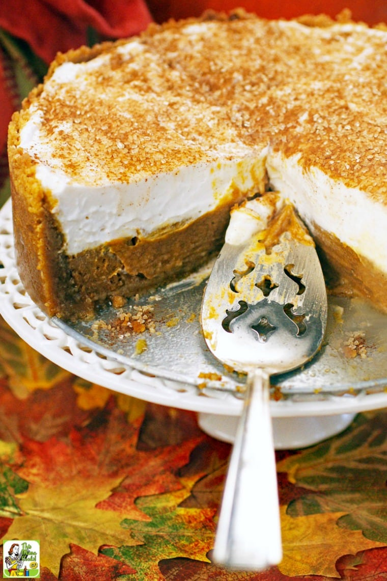 A cake stand and serving spoon with a deep dish pumpkin pie.