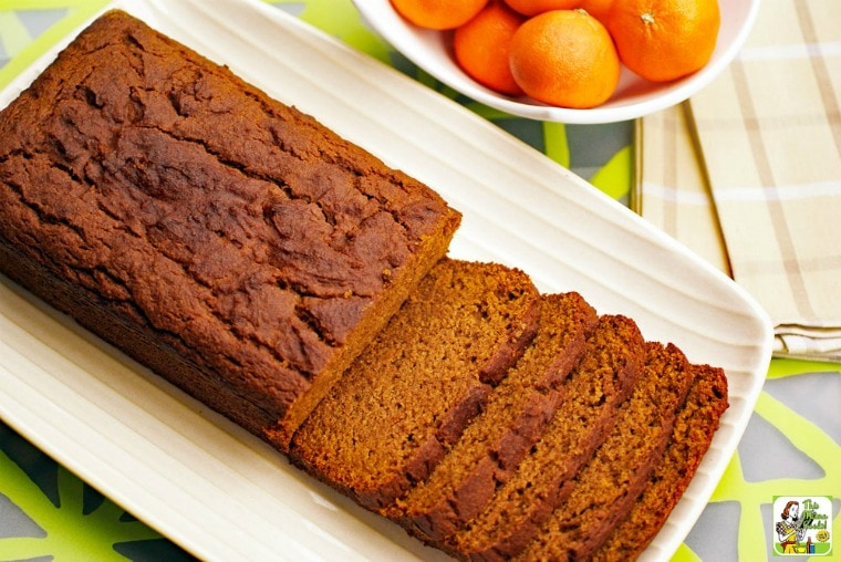 Overhead shot of a Pumpkin Bread sliced up on a white plate with a bowl of tangerines