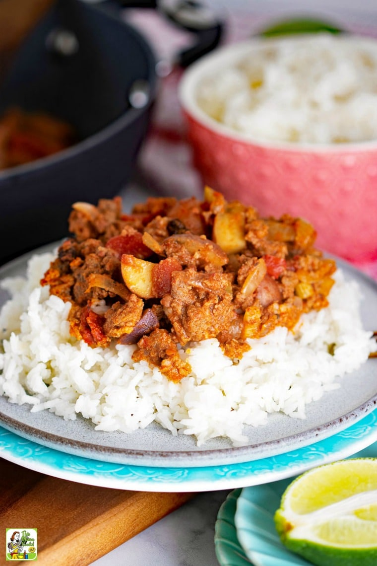 Mexican Picadillo on a plate with white rice, a pink bowl of rice, and a frying pan of picadillo