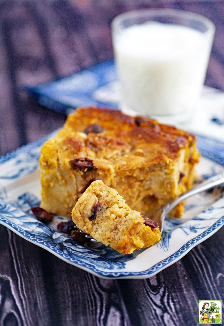 Gluten free bread pudding recipe with pumpkin on a blue and white plate with a fork and a glass of milk in the background.