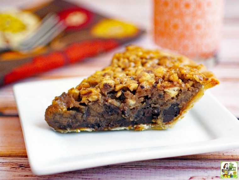 A slice of Gluten Free Chocolate Pecan Pie on a white plate with fork, napkin and glass of milk in the background.