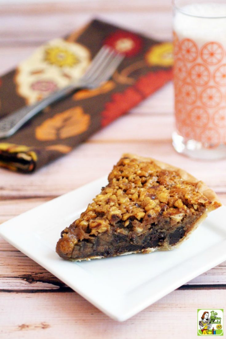 A slice of chocolate gluten free pecan pie on a square white plate with a glass of milk and napkin in the background.