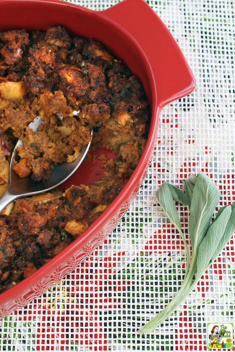 A red casserole dish of Thanksgiving stuffing with serving spoon and a sprig of sage on a festive holiday tablecloth.