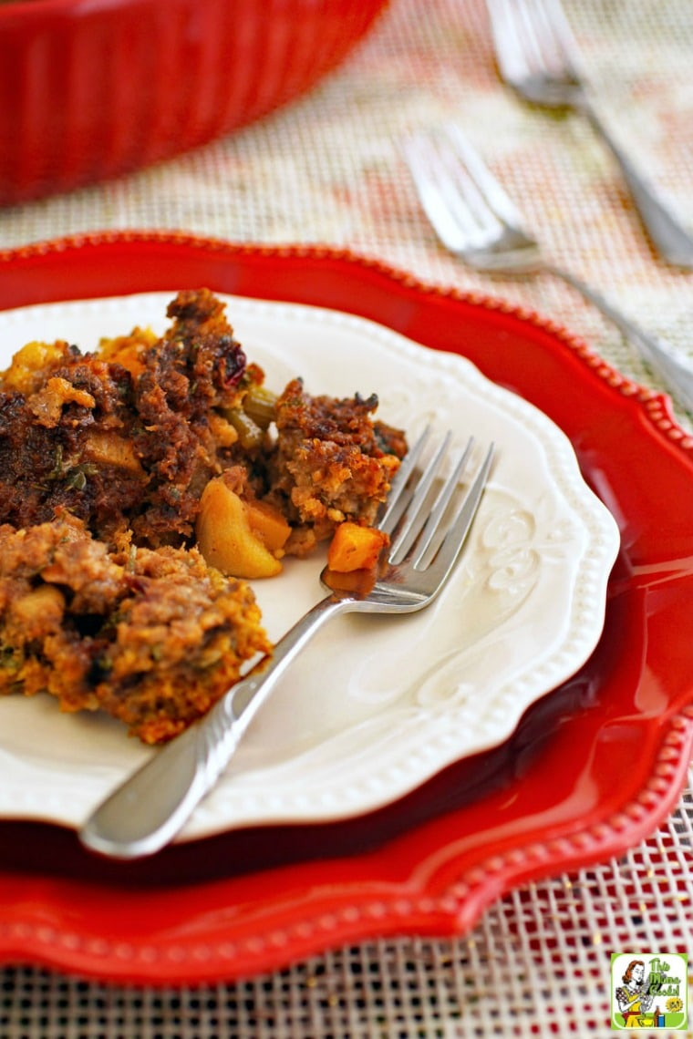 A plate of gluten free stuffing with fork on a larger red plate with casserole dish and serving forks in the background.