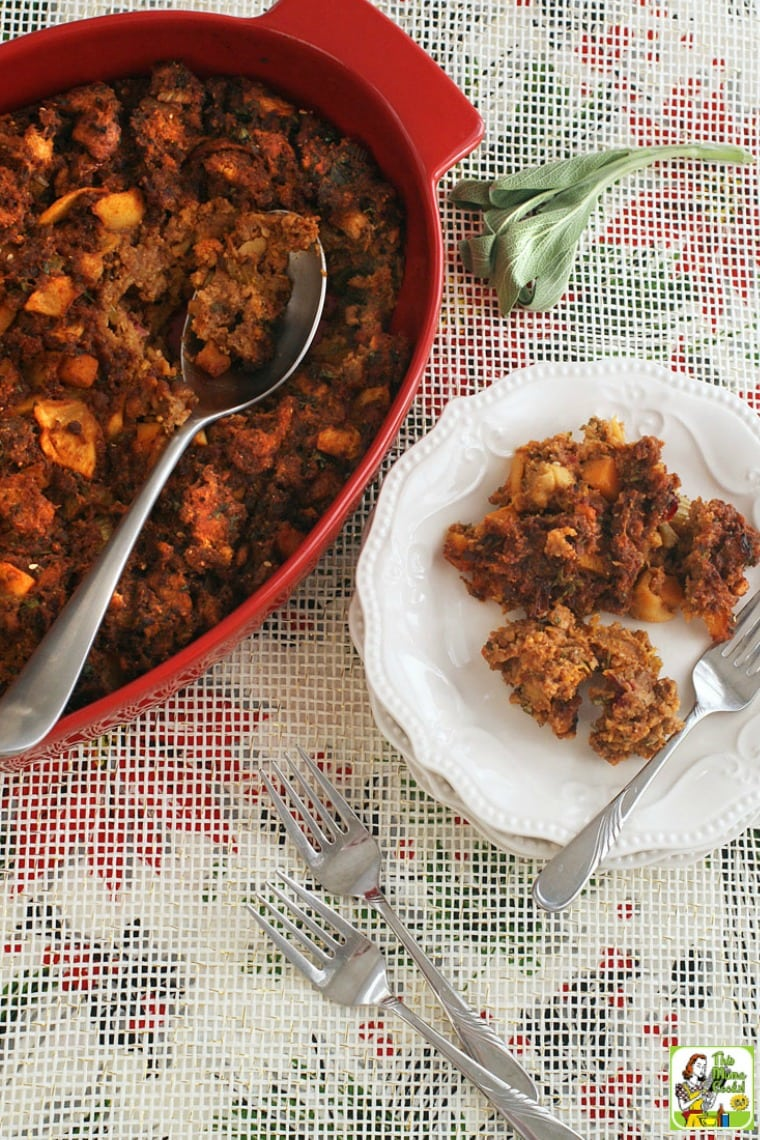 A holiday plate and casserole dish of gluten free stuffing with shorizo, squash and apples with forks.