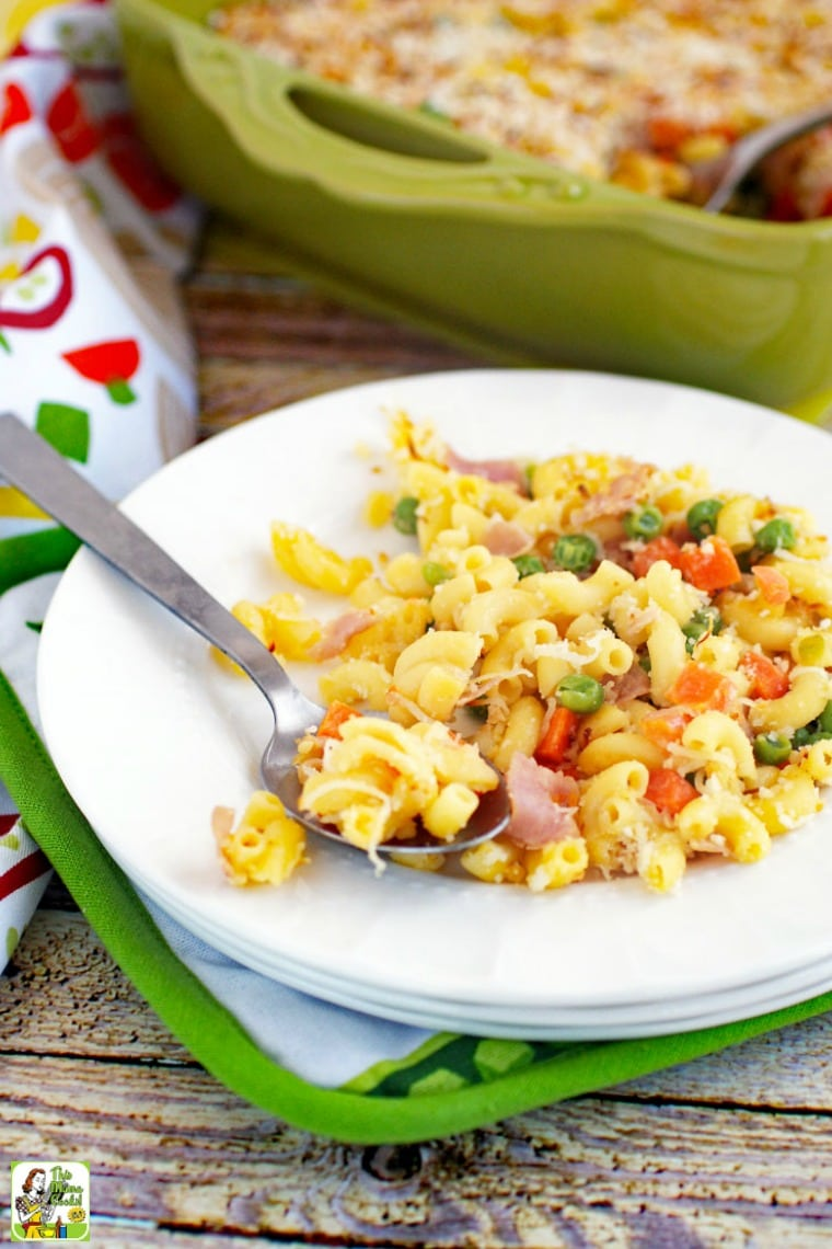A white plate of mac and cheese with peas, carrots & ham