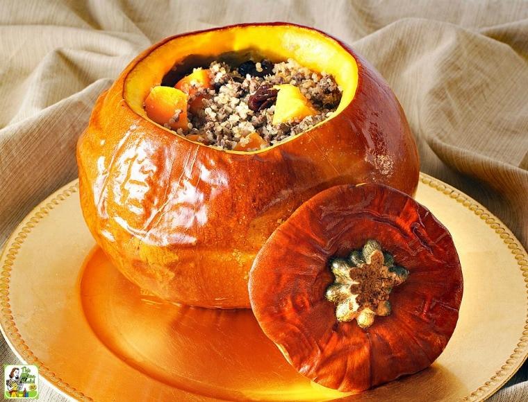 Baked Stuffed Pumpkin stuffed with quinoa, venison, dried cherries, and butternut squash, on a golden platter.