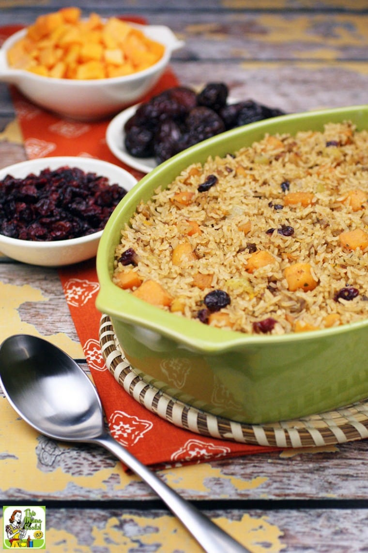 Greem casserole dish of vegan rice stuffing with bowls of cranberries, butternut squash and dates