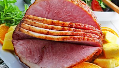 Closeup of crockpot spiral ham on a plate with slices of oranges and pineapple.