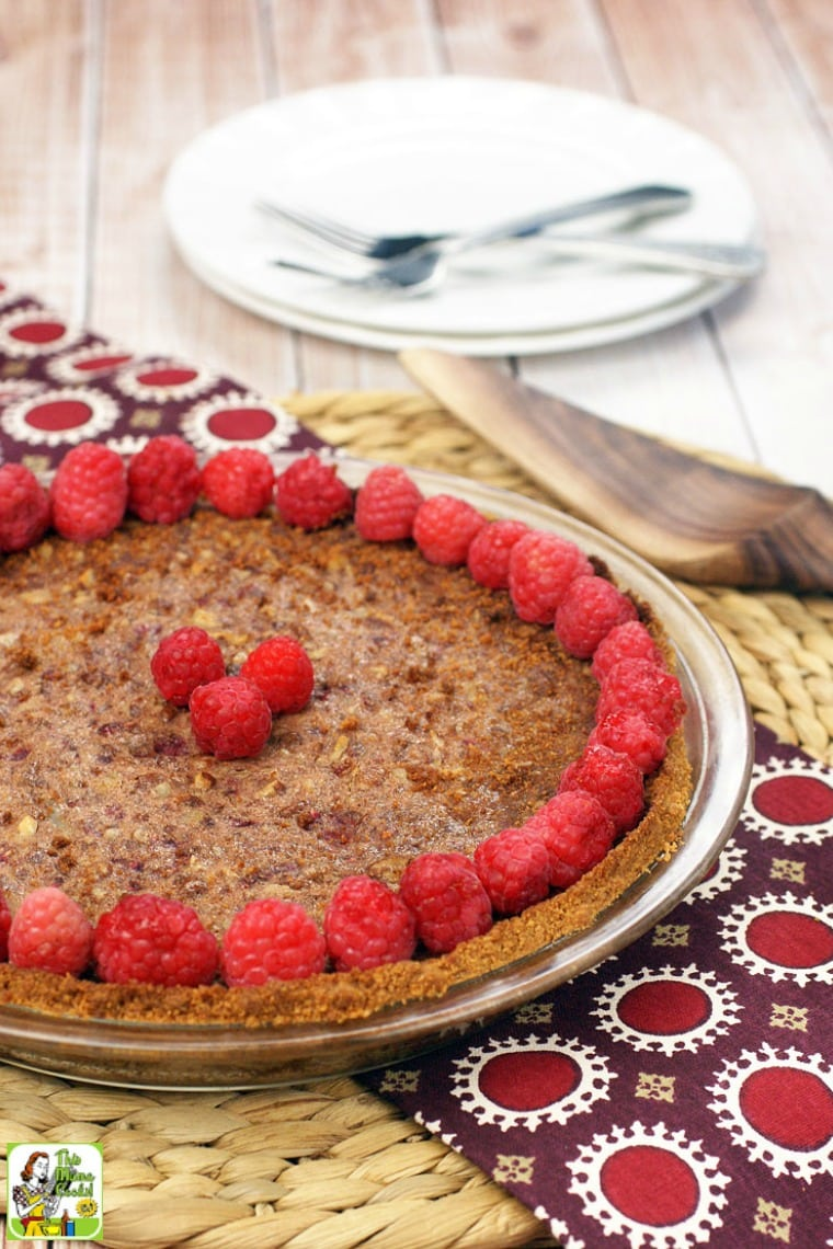 Gluten free pecan pie with raspberries, plates, forks, and pie server.