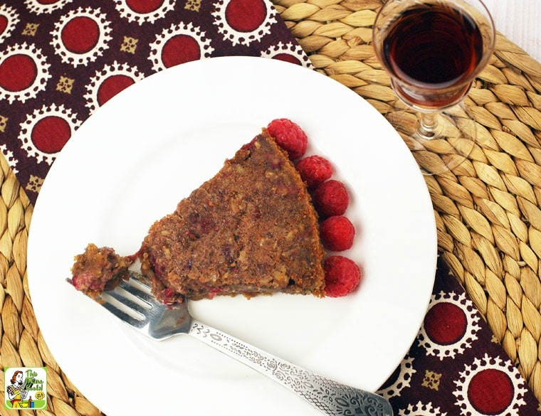 Overhead of a slice of Raspberry Pecan Pie on a white plate with a fork and a glass of port