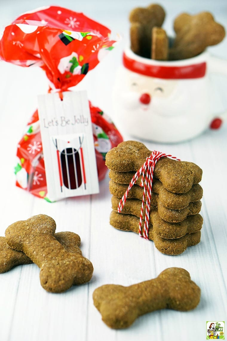 Holiday dog biscuits and treats in a Santa mug, wrapped in string, and in a gift bag.