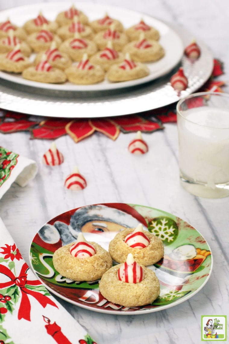 Two holiday plates of Peppermint Thumbprint Hershey Kiss Cookies with a glass of milk.