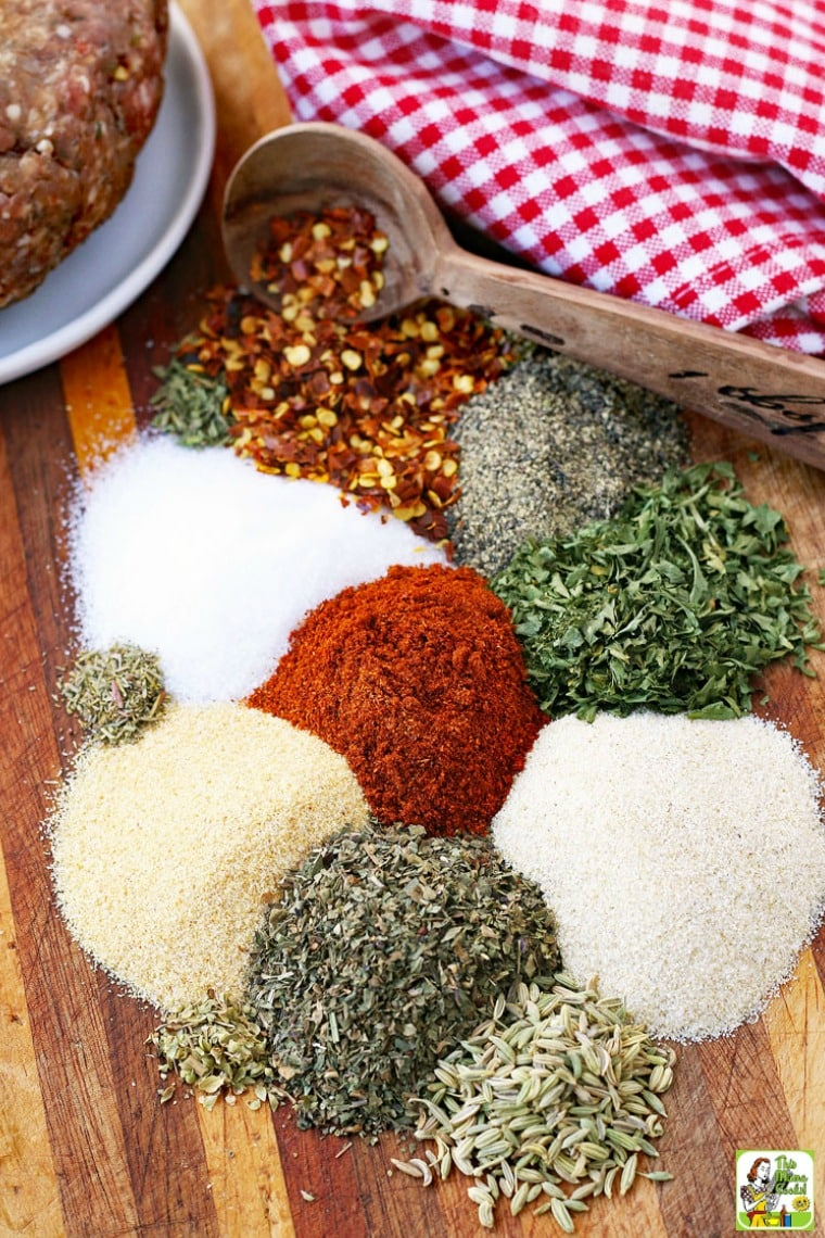 Small mounds of spices and seasonings, a measuring spoon, a checked napkin, and the edge of a bowl with ground meat, sitting on a wooden cutting board.