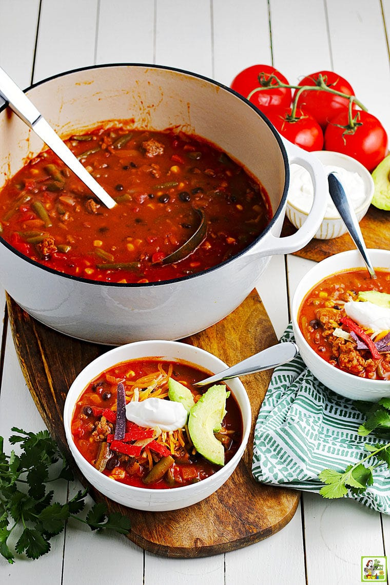 A large Dutch oven of taco soup with cooking spoon and two white bowls of soup with spoons on a wooden cutting board with a napkin with tomatoes in the background.