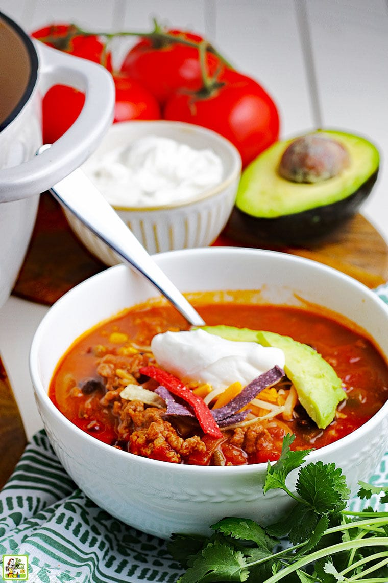 Closeup of a bowl of taco soup with spoon, dollop of sour cream, slice of avocado, and pieces of tortilla chips with a bowl of sour cream, avocado and tomatoes in the background.