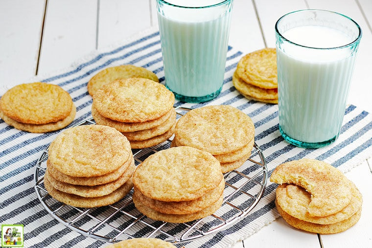 Stacks of Rice Flour Snickerdoodles Cookies on a wire rack and striped napkin with glasses of milk.