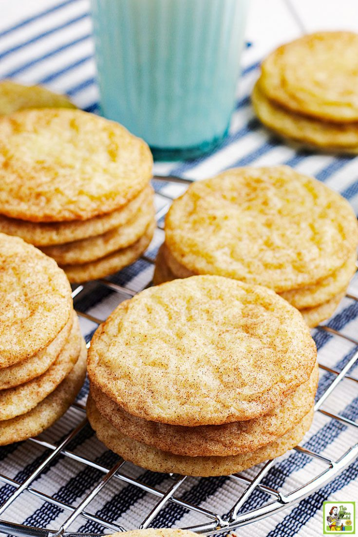 Stacks of rice flour snickerdoodles cookies on a striped napkin with a glass of milk.