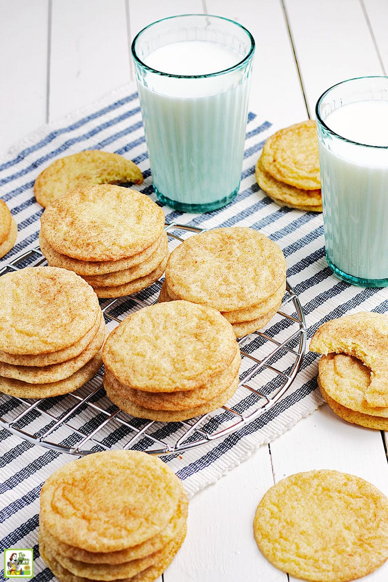 Stacks of snickerdoodles cookies on a striped napkin with glasses of milk.
