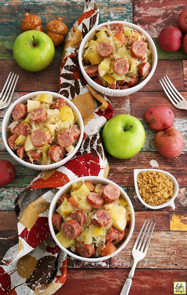 White bowls of slow cooker sauerkraut, sausage, potatoes, and apples with napkins and forks.