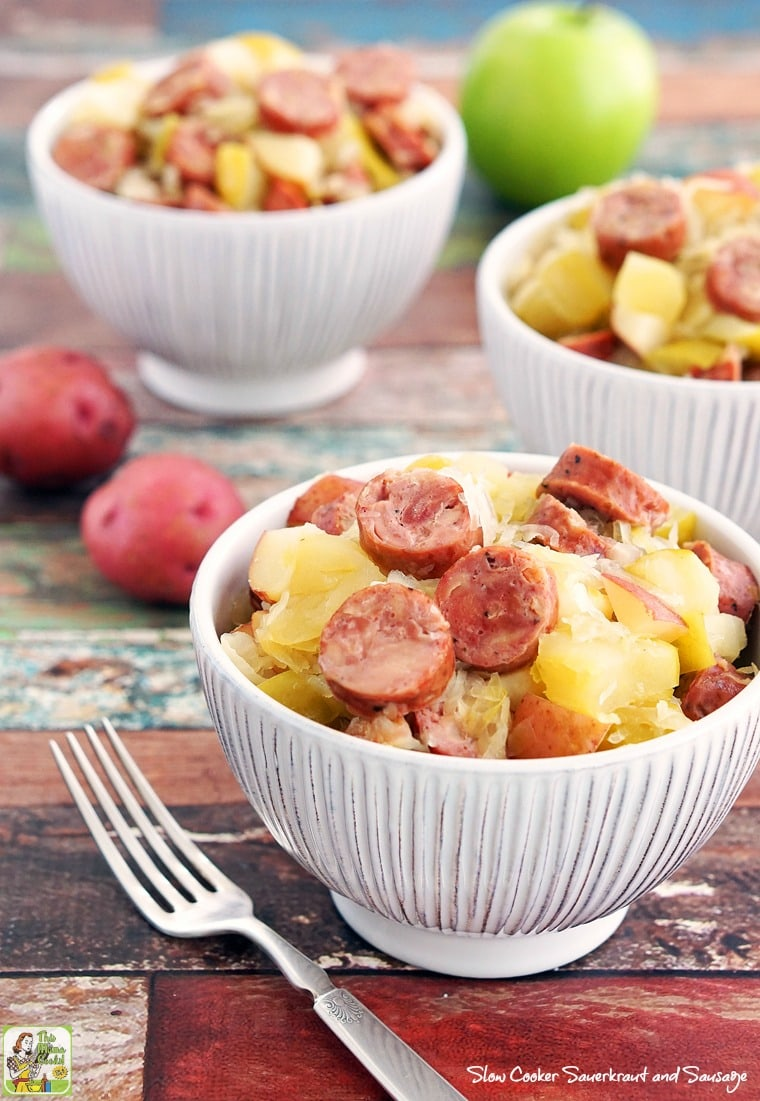 Three white bowls of crock pot sausage, sauerkraut, potatoes, and apples with a forks, red potatoes, and green apple..