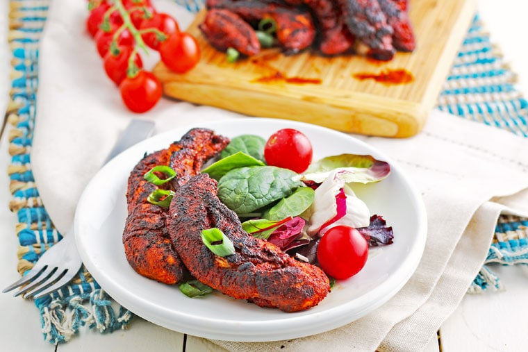 A plate of Blackened Chicken Tenders with salad and tomatoes with wooden cuttin board and more chicken in the background.