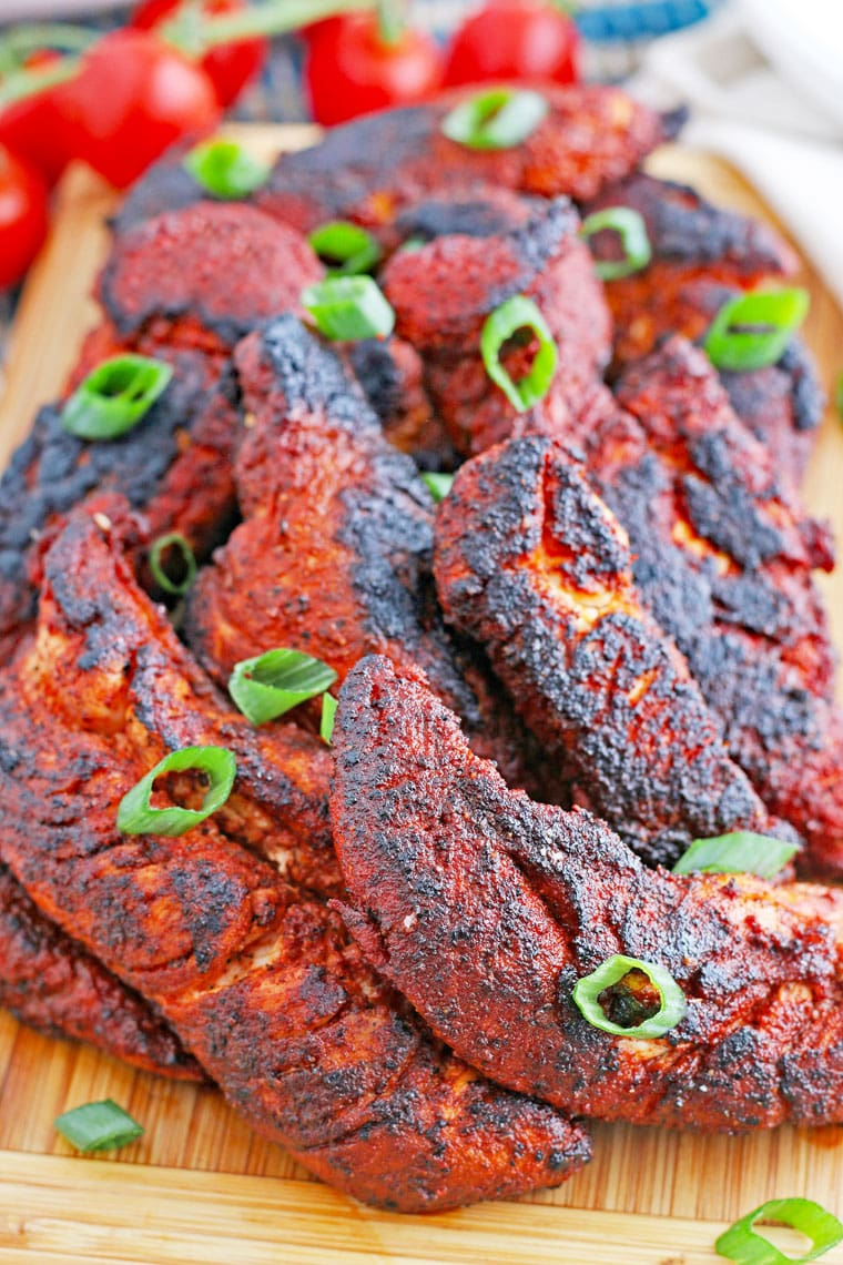 A pile of blackened chicken tenders on a wooden cutting board.