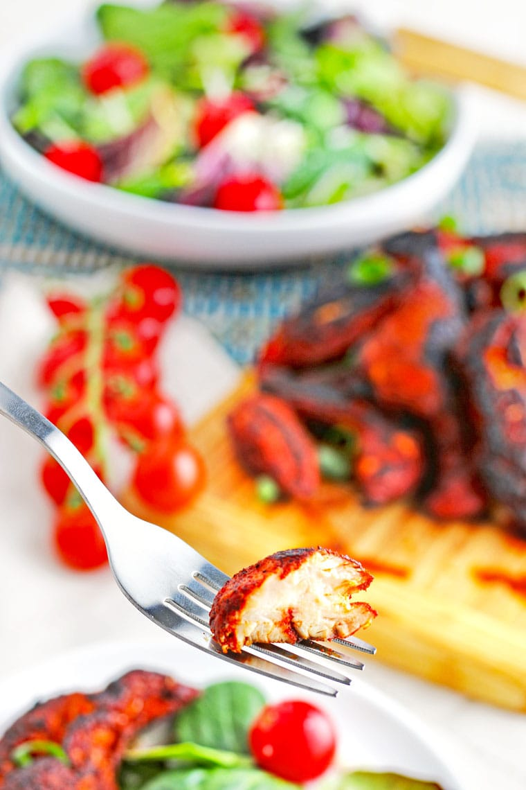 Closeup of a fork of blackened chicken with a bowl of salad, tomatoes, and blackened chicken tenders on a wooden board in the background.