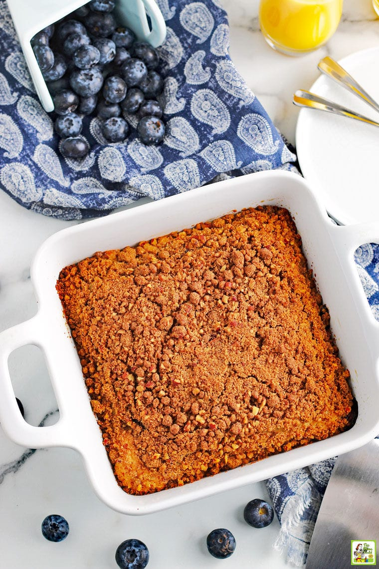 Overhead shot of a baking dish of blueberry muffin cake with blue napkin, glass of orange juice, white plates, forks, cake server, and blueberries.