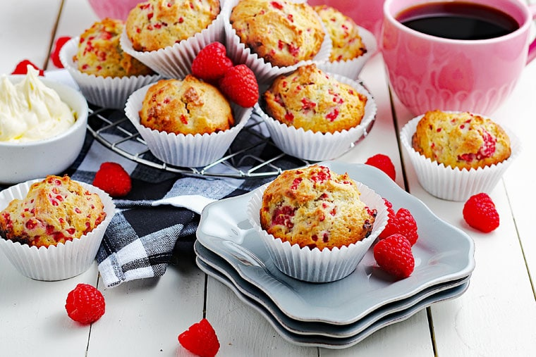 A tabletop of raspberry yogurt muffins with a black and white napkin, fresh raspberries, white plates, a bowl of butter, and pink mugs of black coffee.