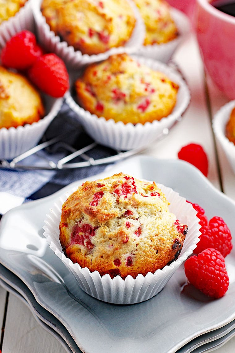 A raspberry muffin on white plates with fresh raspberries with more raspberry muffins in white cupcake liners in the background.