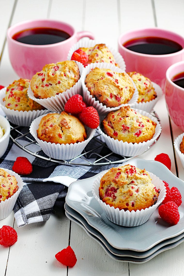 A tabletop with muffins in white cupcake liners on white plates and on black and white napkins with red raspberries and pink mugs of black coffee.